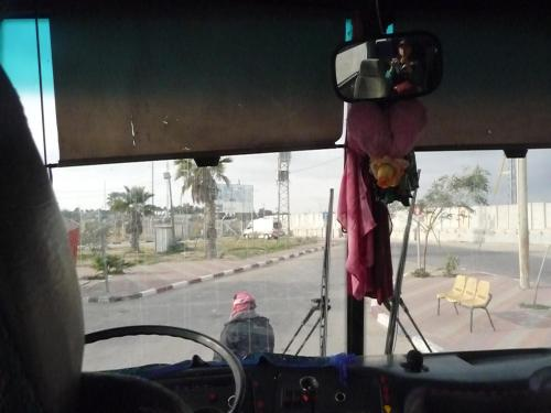 Lora in the rearview mirror shooting a picture from the bus in no-man's land between Gaza and Egypt.