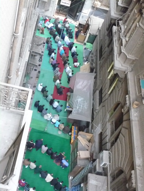 Muslims praying in downtown Cairo at a small neighborhood Mosque.