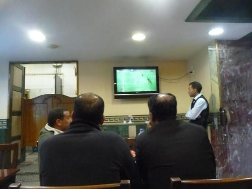 Patrons and waiter watching futbol in restaurant