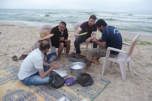 Young Palestinian men enjoying a BBQ at the beach in Gaza.