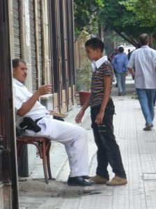Egyptian policeman holding his prayer book answers a boy's question.