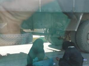 Two women sitting under a large truck in the Sinai