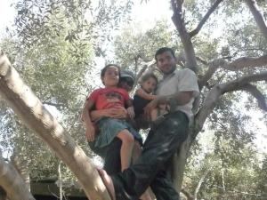 Lora and Motasem and children in the olive tree