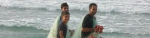 Palestinian fisherman with his sons carrying nets.