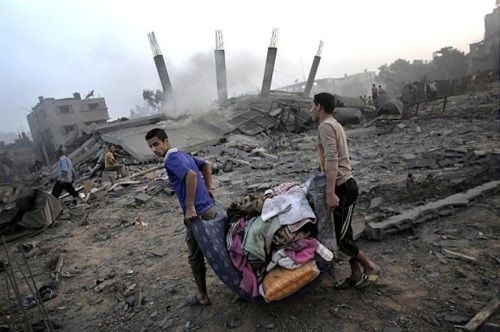 Palestinians collect their belongings from damaged houses in Gaza City. (Photo: Mahmud Hams / AFP / Getty Images).  ABC News in the US later misidentified this picture as showing Israeli victims.