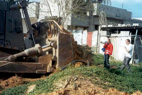 Picture taken between 3:00-4:00PM, 16 March 2003, Rafah, Occupied Gaza. Rachel Corrie (L) and Nick (R) oppose the potential destruction of this home (to the west of the Doctor's home where Rachel was killed). In the instance pictured, the bulldozer did not stop and Rachel was pinned between the scooped earth and the fence behind her. On this occasion, the driver stopped before seriously injuring her. Photo by Joseph Smith (ISM Handout).