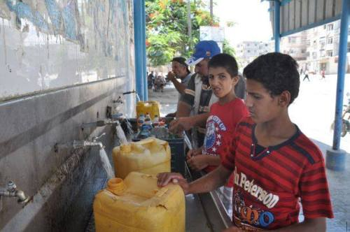 Photo 1: Water crisis in Gaza Strip, Palestinian Childs packaged drinking water from a UNRWA school due to the interruption of water from their homes during the recent war in July-August 2014.