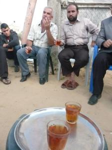 Palestinian whose house was destroyed by Israel the day before offers tea to his neighbors sitting amid the ruins.
